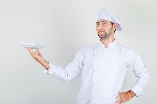 Männlicher koch in der weißen uniform, die aufwirft, während platte hält und stolz schaut