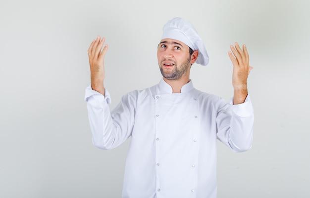 Männlicher koch in der weißen uniform, die erhobene hände hält und dankbar schaut