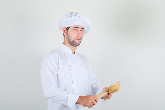 Männlicher koch in der weißen uniform, die holzlöffel und nudelholz hält