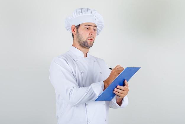 Männlicher koch in der weißen uniform, die notizen auf zwischenablage macht und beschäftigt schaut
