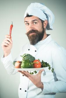 Männlicher koch in kochuniform hält zwiebel in der hand lebensmittelservice bio-lebensmittel-profi für gesunde ernährung