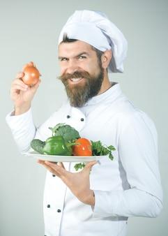 Männlicher koch in kochuniform mit lächeln hält zwiebel in der hand und koch für vegetarische ernährung