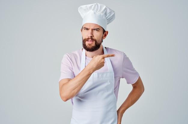 Männlicher koch in küchenschürzen, der restaurantfachleute kocht