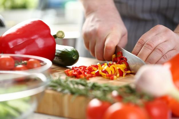 Männlicher koch in schürze geschnittenen roten und gelben pfeffer