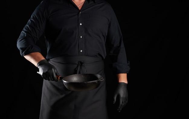 Männlicher koch in schwarzer uniform und latexhandschuhen hält eine leere runde vintage-pfanne aus schwarzem gusseisen vor sich, zurückhaltend
