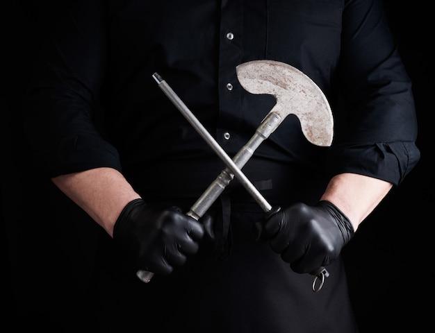 Männlicher koch in schwarzer uniform und schwarzen latexhandschuhen hält ein großes scharfes vintage-messer für fleisch und gemüse und einen metallschärfer für messer