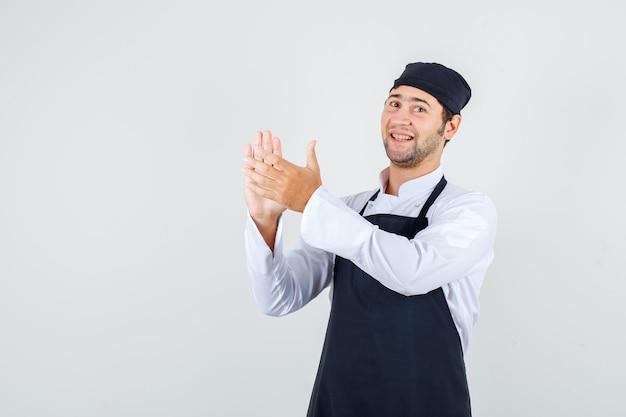 Männlicher koch in uniform, schürze applaudiert nach dem dienst und schaut fröhlich, vorderansicht.