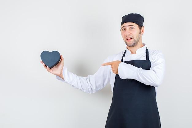 Männlicher koch in uniform, schürze, die finger auf schwarze geschenkbox zeigt, vorderansicht.