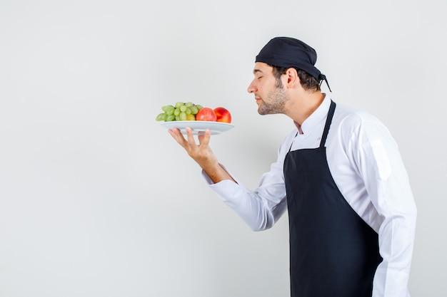 Männlicher koch in uniform, schürze, die früchte im teller riecht, vorderansicht.