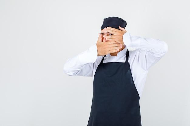 Männlicher koch in uniform, schürze, die gesicht bedeckt und durch finger schaut, vorderansicht.