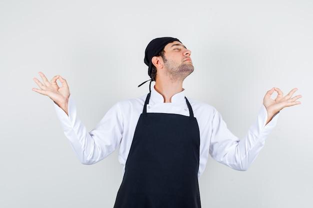 Männlicher koch in uniform, schürze, die hände in der yoga-geste hält und entspannt, vorderansicht schaut.