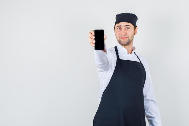 Männlicher koch in uniform, schürze, die handy zeigt und fröhlich schaut, vorderansicht.