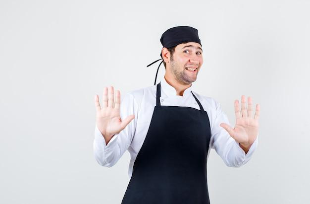 Männlicher koch in uniform, schürze, die höflich verweigerungsgeste zeigt, vorderansicht.