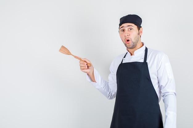 Männlicher koch in uniform, schürze, die hölzernen spatel hält und überrascht, vorderansicht schaut.