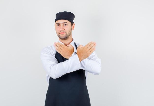 Männlicher koch in uniform, schürze, die stoppgeste zeigt, vorderansicht.
