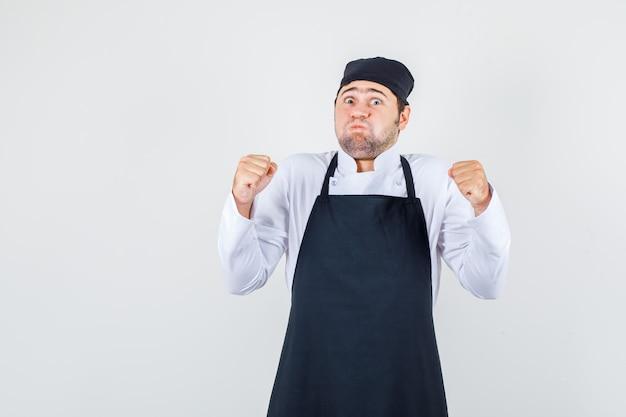 Männlicher koch in uniform, schürze, die wangen mit geballten fäusten bläst, vorderansicht.