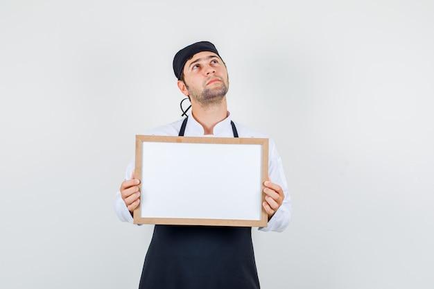 Männlicher koch in uniform, schürze, die weiße tafel hält und nachdenklich, vorderansicht schaut.