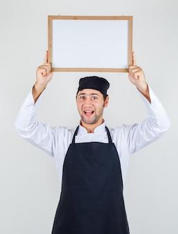 Männlicher koch in uniform, schürze, die weiße tafel über kopf hält und fröhlich schaut, vorderansicht.