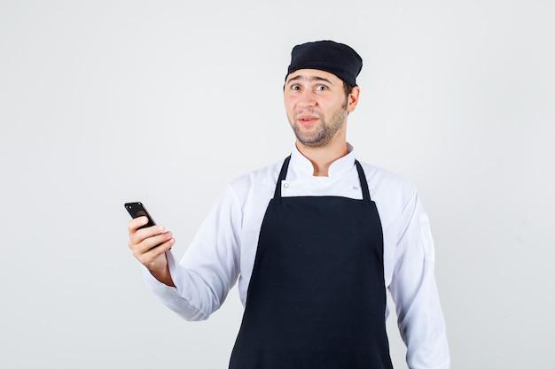 Männlicher koch in uniform, schürze hält handy und schaut glücklich, vorderansicht.