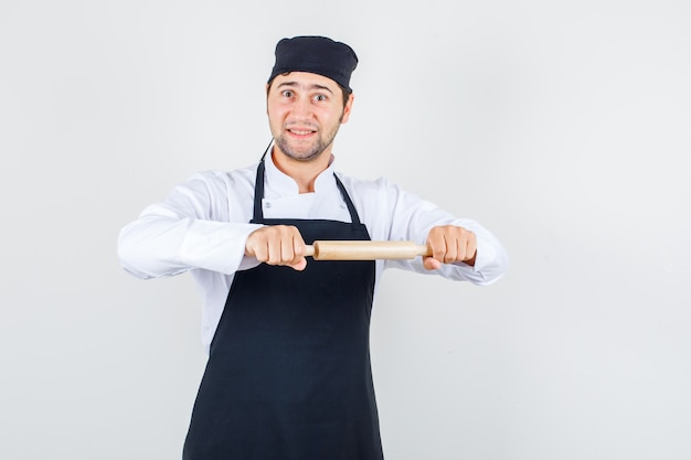 Männlicher koch in uniform, schürze hält nudelholz und schaut fröhlich, vorderansicht.
