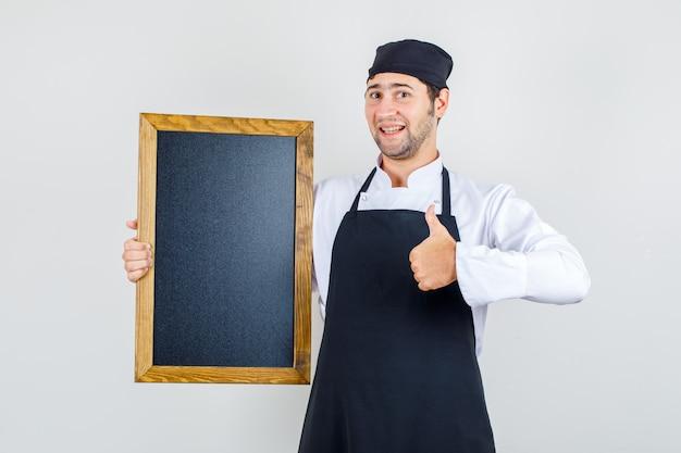 Männlicher koch in uniform, schürze hält tafel mit daumen hoch und schaut froh, vorderansicht.