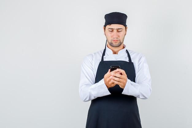 Männlicher koch in uniform, schürze mit smartphone und ernsthafter vorderansicht.