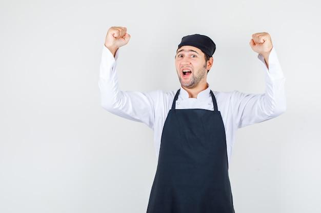 Männlicher koch in uniform, schürze schreit und zeigt siegergeste und schaut glücklich, vorderansicht.