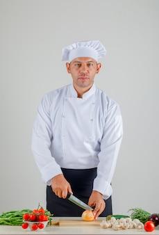 Männlicher koch in uniform, schürze und hut, die zwiebel auf holzbrett in der küche schneiden