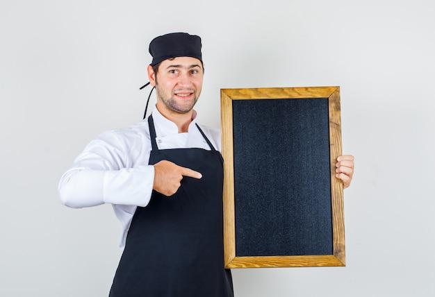 Männlicher koch in uniform, schürze zeigt auf tafel und schaut fröhlich, vorderansicht.