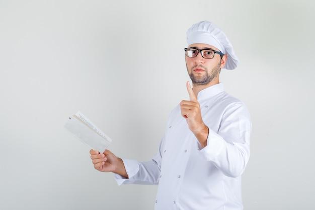 Männlicher koch in weißer uniform, brille, die buch mit wartender geste hält