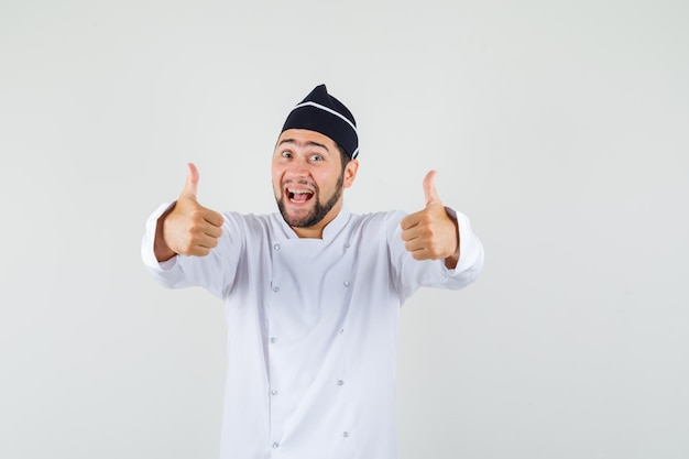 Männlicher koch in weißer uniform, der daumen nach oben zeigt und fröhlich aussieht, vorderansicht.