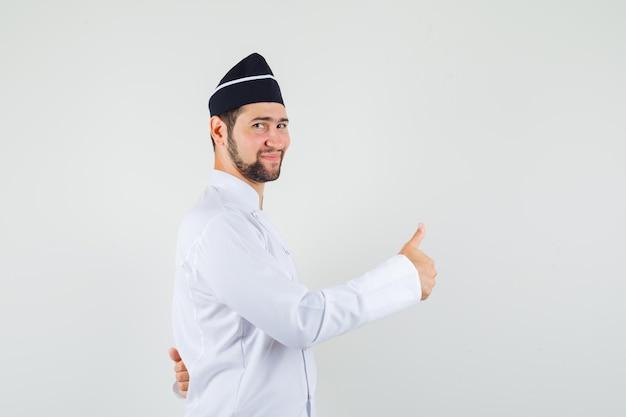 Männlicher koch in weißer uniform, der daumen nach oben zeigt und zufrieden aussieht.