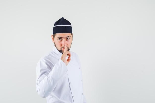 Männlicher koch in weißer uniform, der stille zeigt und vorsichtig aussieht, vorderansicht.