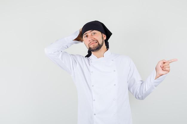 Männlicher koch in weißer uniform, der zur seite zeigt und unentschlossen aussieht, vorderansicht.