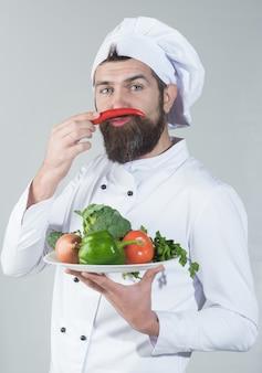 Männlicher koch in weißer uniform hält pfeffer neben dem gesicht gesunder ernährung und bärtigem küchenkonzept