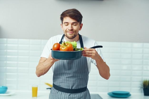 Männlicher koch kocht in der küche, gesundes hausgemachtes essen