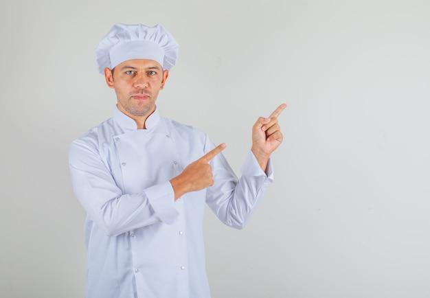 Männlicher koch kocht in hut und uniform, die finger auf etwas zeigen und selbstbewusst aussehen