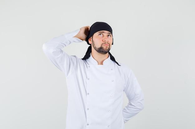Männlicher koch kratzt sich am kopf, während er in weißer uniform nach oben schaut und nachdenklich aussieht, vorderansicht.