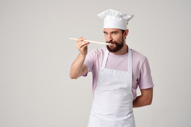 Männlicher koch mit einer mütze auf dem kopf, der professionelles essen schmeckt. foto in hoher qualität