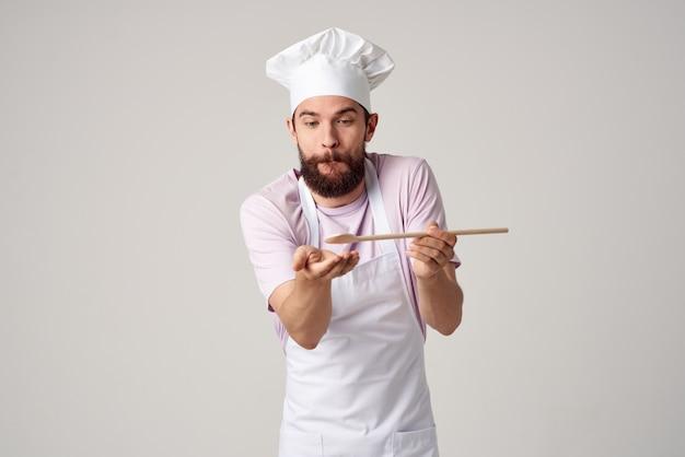 Männlicher koch mit einer mütze auf dem kopf, der professionelles essen schmeckt