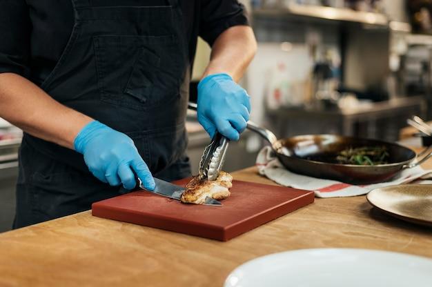 Männlicher koch mit handschuhen, die fleisch hacken