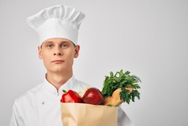 Männlicher koch mit lebensmittelpaket gesunde lebensmittelküche