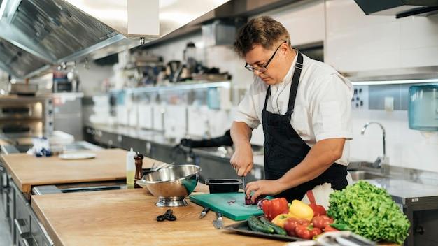Männlicher koch mit schürze, die gemüse hackt