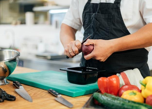 Männlicher koch mit schürze, die gemüse schneidet