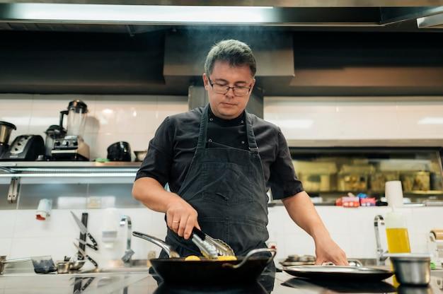 Männlicher koch mit schürze, die nudeln kocht