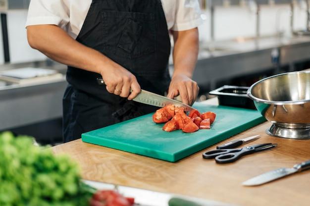 Männlicher koch mit schürze, die tomaten in der küche schneidet