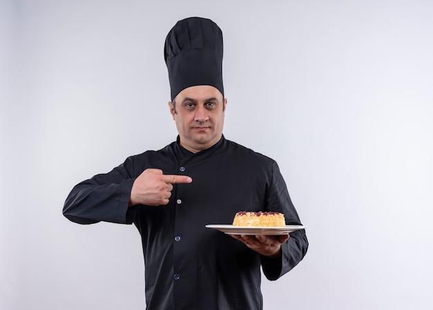 Männlicher koch mittleren alters in kochuniform zeigt auf kuchen auf teller in seiner hand auf isolierter weißer wand mit kopienraum