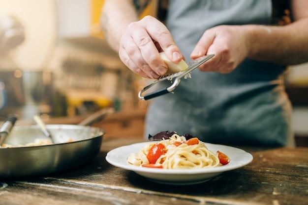 Männlicher koch reibt käse in den teller mit frisch gekochten nudeln, pfanne auf hölzernem küchentisch. hausgemachte fettuccine zubereitung. traditionelle italienische küche