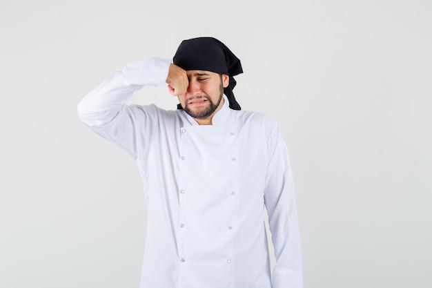 Männlicher koch reibt sich das auge, während er wie ein kind in weißer uniform weint und beleidigt aussieht. vorderansicht.