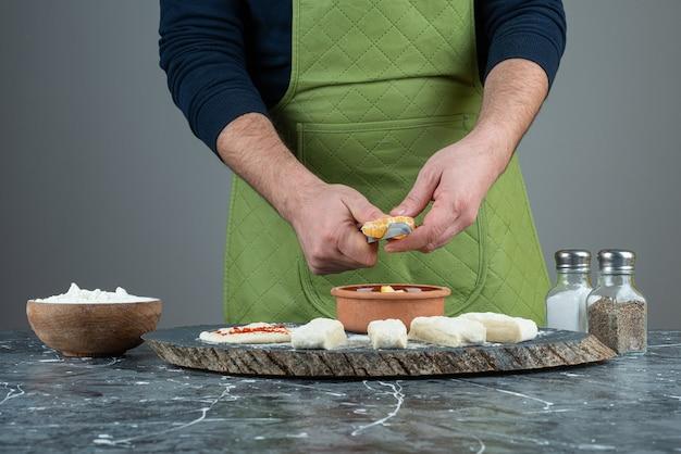 Männlicher koch schneidet orange in die stücke auf marmortisch.